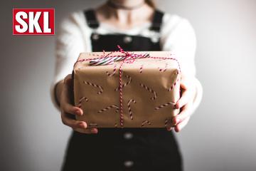 200.000 € Bescherung im Dezember. Frau in dunkler Latzhose steht vor einem grauen Hintergrund und hält ein Geschenk in die Kamera. Verpackt in braunem Papier mit Rot Weißen Zuckerstangen.
