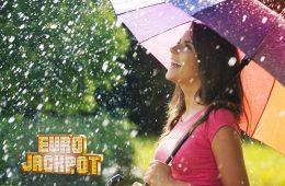 Frau mit buntem Regenschirm im Regen