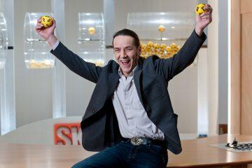 Gewinner mit Lottokugeln in den Händen