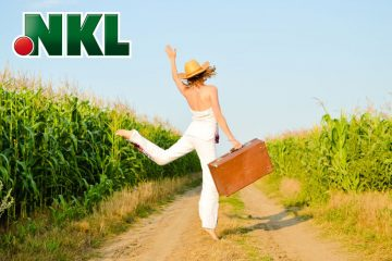 Junge Frau mit Koffer in der Hand läuft jubelnd über Feldweg