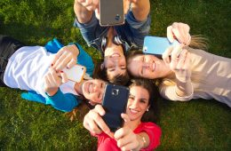 Junge Leute liegen mit Smartphone auf der Wiese