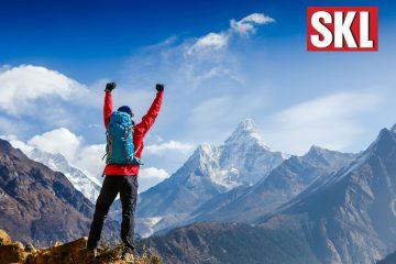 Mann auf dem Gipfel im Gebirge