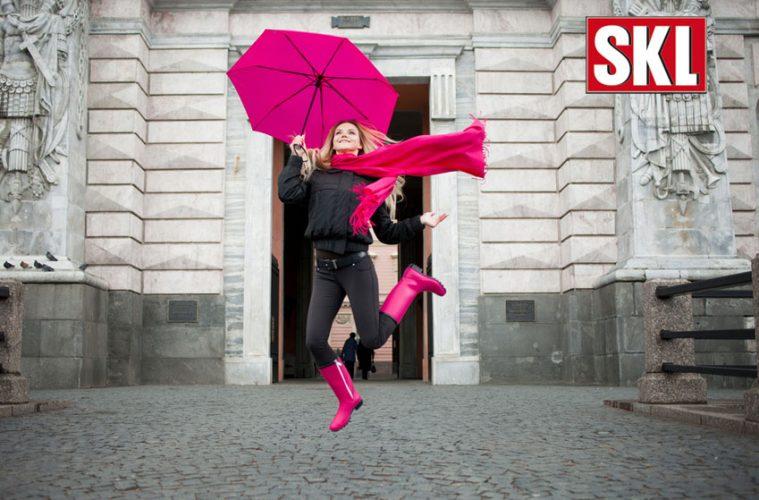 Junge Frau mit Regenschirm springt hoch