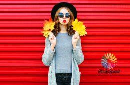 Junge Frau mit Herbst-Blättern in den Händen