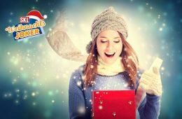 Frau öffnet Weihnachtsgeschenk