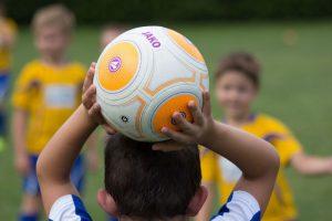 Kind hält Fußball über dem Kopf