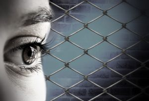 weibliches Gesicht vor Zaun