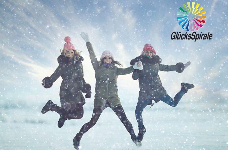 Drei junge Frauen springen im Schnee in die Höhe
