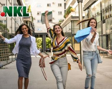 Drei junge Frauen glücklich mit Shopping-Tüten in der Stadt