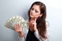 Nachdenkliche Frau mit aufgefächerten Dollar-Scheinen in der Hand