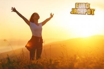 Junge Frau streckt Arme in den Himmel auf einer Wiese bei Sonnenuntergang