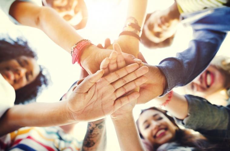 Glückliche Menschen legen Hände aufeinander
