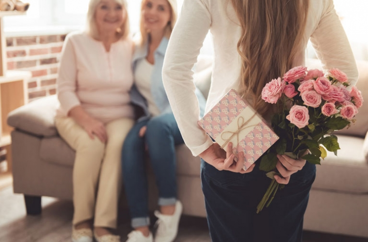 Tochter überrascht Mutter mit Blumenstrauß und Geschenk am Muttertag