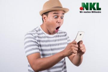 Junger Mann schaut überrascht auf sein Telefon