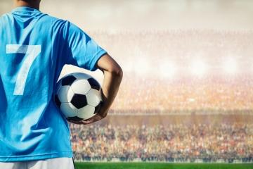 Fußballspieler mit Trikotnummer 7 blickt auf Menschenmenge im Stadion