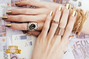 reiche Frau mit Goldschmuck legt Hände auf 500-Euro-Geldscheine
