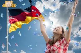 Frau mit Deutschland-Flagge steht im Geldregen
