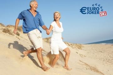 Glückliches Rentner-Paar läuft am Strand entlang