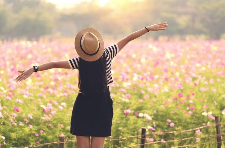 Junge Frau schaut auf Blumenwiese und genießt Freiheit