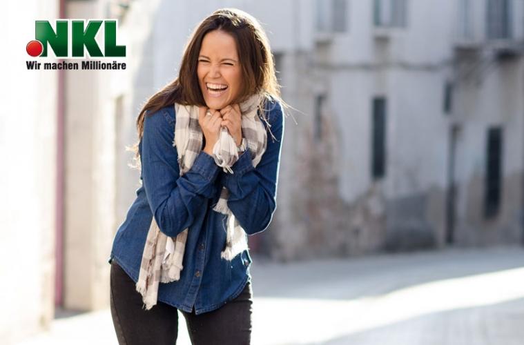 Junge Frau lacht und freut sich über einen Gewinn