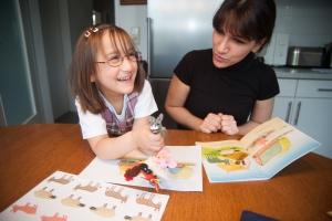 Mädchen lernt am Tisch mit Mutter in der Küche
