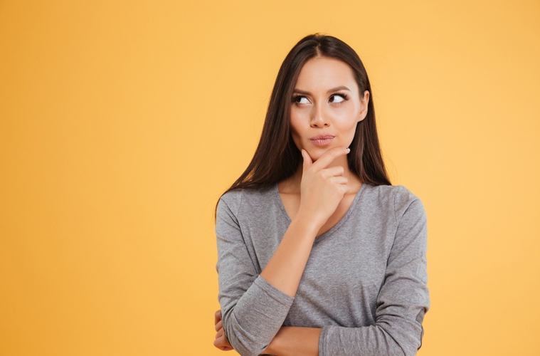 Junge Frau in Denkpose vor gelbem Hintergrund