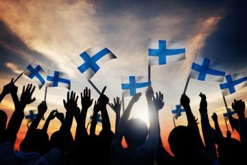Menschen strecken finnische Flaggen in die Höhe.