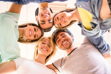 Glückliche junge Menschen, die im Kreis stehen und die Köpfe aneinander lehnen.