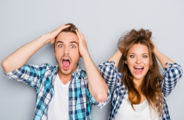 Mann und Frau schlagen vor Überraschung Hände über dem Kopf zusammen
