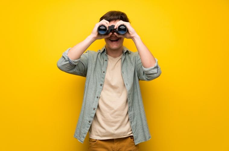 Mann mit Fernglas vor einer gelben Wand