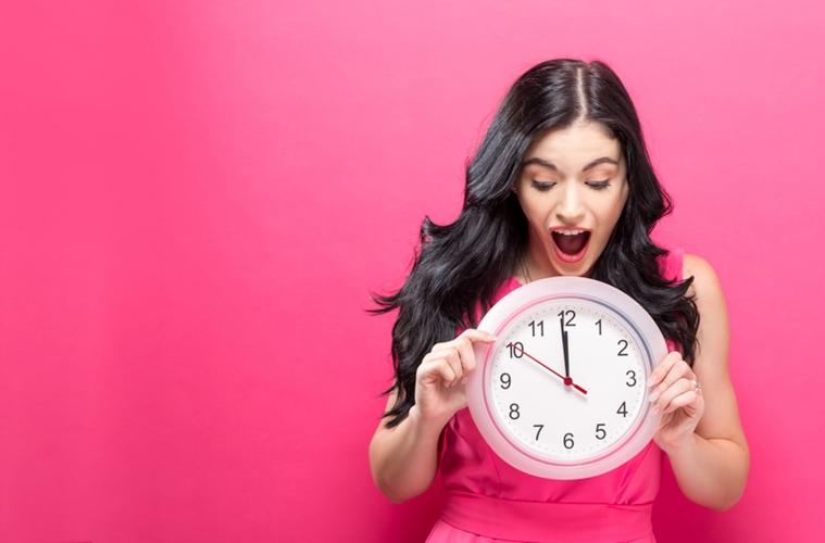 Junge Frau vor pinkem Hintergrund zeigt auf eine Uhr, wo es 5 vor 12 ist.