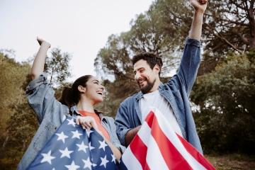 Junge Frau und junger Mann mit US-Flagge strecken die Arme in die Luft.