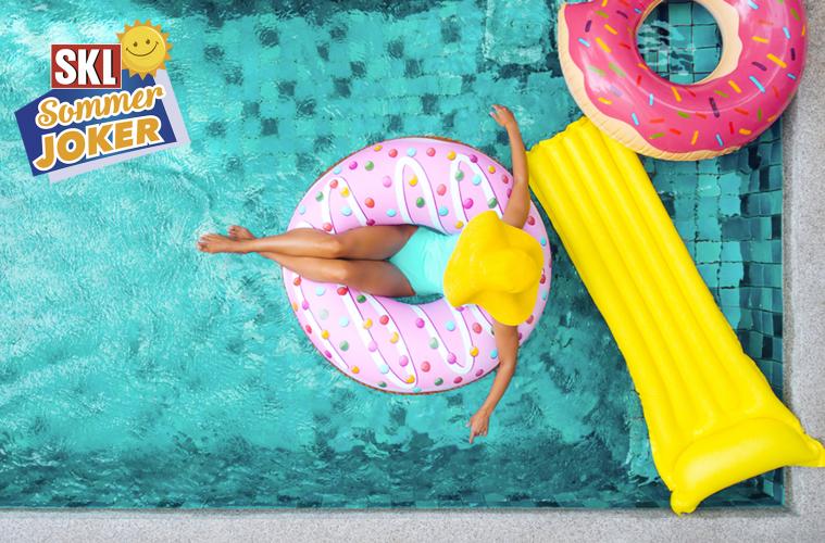 Frau mit gelbem Sonnenhut im Pool auf einem Donut-Schwimmreifen