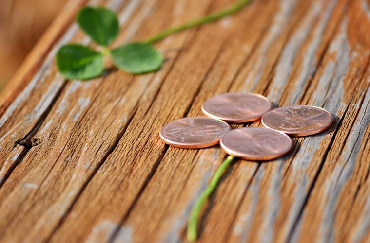 Auf einem Holztisch liegen ein Kleeblatt und 4 kupferne Münzen in Form eines Kleeblatts