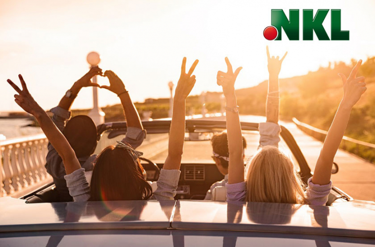 Junge Leute in Cabriolet fahren jubelnd Sonnenuntergang entgegen