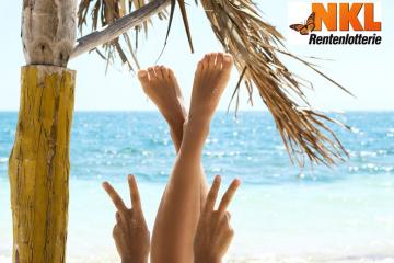Frau streckt Füße in die Luft am Strand
