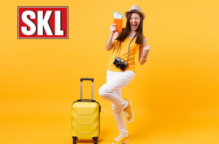 Glückliche, junge Touristin mit Gewinner-Geste