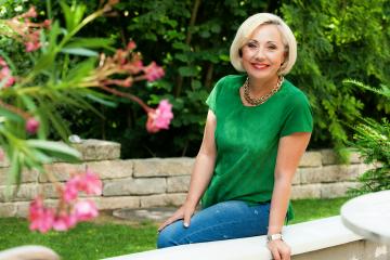 SKL-Los, SKL Millionärin Vesca Vekic sitzt lächelnd in ihrem Garten ihrer Villa in München