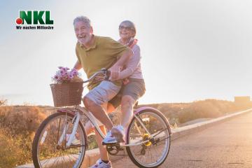 Älteres Ehepaar fährt im Sommer mit dem Fahrrad im Sonnenuntergang. Sie lachen und sind glücklich.