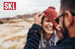 Glückliches Pärchen im Winter. Lachende Frau mit Mütze. Freuen sich über Gewinn.