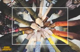 Gruppe von Menschen legen ihre Hände aufeinander. Einer für alle und alle für einen. Eurojackpot