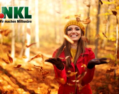 Frau freut sich über Extra-Einkommen der NKL. Herbstlich, Blätter, Freude.