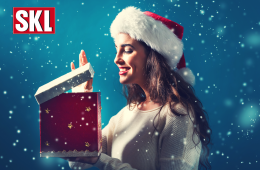 Fröhliche junge Frau, die eine Weihnachtsgeschenkbox öffnet.
