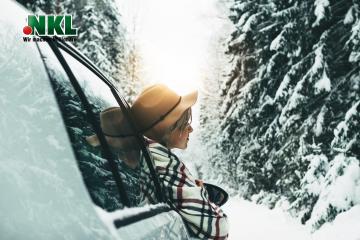 Schöne FRau fährt im Winter mit dem Auto durch Schnee.