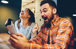 Aufgeregte männliche und weibliche Hipster freuen sich über den Gewinn einer Internet-Lotterie Wetten auf der Website auf modernes Smartphone.Glückliches Paar in Liebe feiern Sieg in Online-Wettkämpfen genießen Erfolg