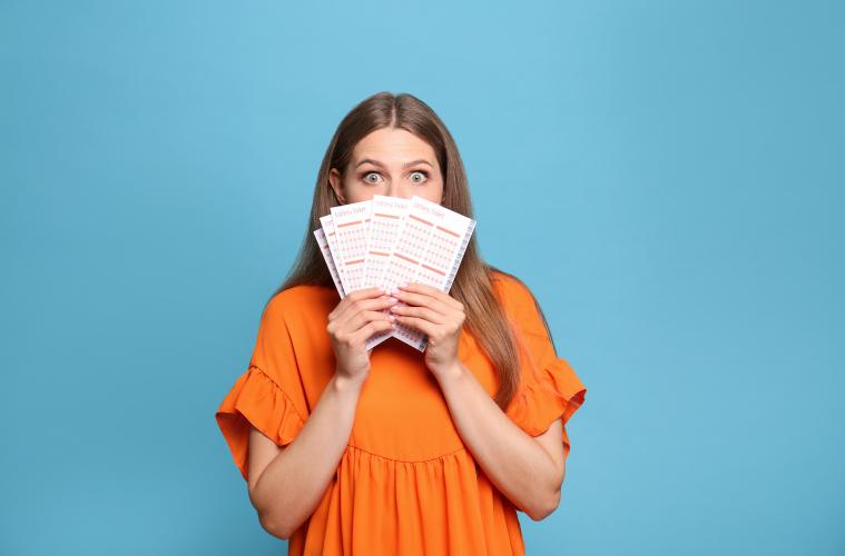 junge Frau mit Lottoschein und orangem Oberteil auf blauem Hintergrund EuroJackpot Gewinn