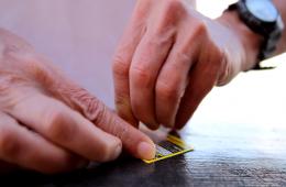 Foto von zwei Händen kratzen ein Rubbel-Los mit flachem Fokus.