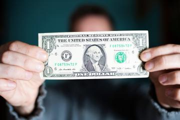 Mann hält eine Dollar Banknote in die Kamera.