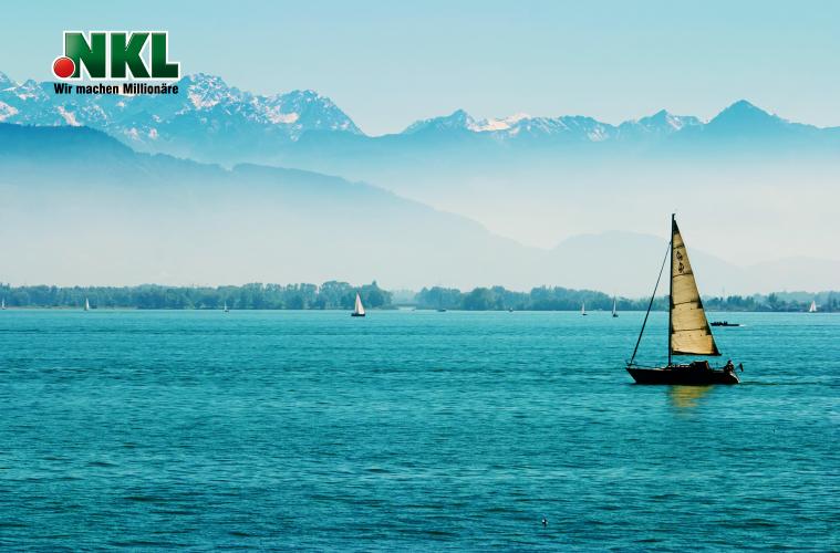 Boote am Bodensee mit den Alpen im Hintergrund. Hennes-Kunde freut sich dort über NKL Renten-Joker Gewinn.