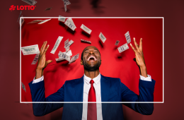 Attraktiver, multiethnischer Mann in schicker, klassischer Jacke blau formalwear trendiger Tuxedo-Ständer mit geschlossenen Augen unter Geldfliegenregen einzeln auf rotem, vivibrierendem Hintergrund erhobene Hände. Lotto-Jackpot Gewinner.